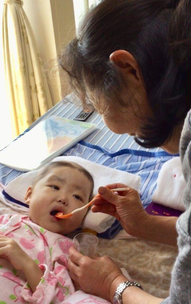 2018年11月25日、おばあちゃんに朝どりのいちごを食べさせてもらう侑花ちゃん(添田さん提供)