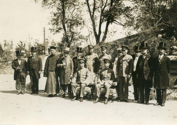 菱刈隆・駐満州国日本大使主催の午餐会に出席し、記念写真撮影に臨んだ昭和天皇の名代・秩父宮親王(椅子の右側)と満州国皇帝康徳帝。椅子の右に立つのは菱刈隆全権大使、左は林権助主席随員=1934年6月8日、
