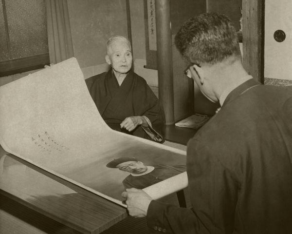 吉田さんから父粛親王の肖像画を贈られなつかしそうにながめる愛新覚羅氏(手前うしろ向きの人)=1962年9月、大阪市住吉区東加賀谷町の吉田さん宅