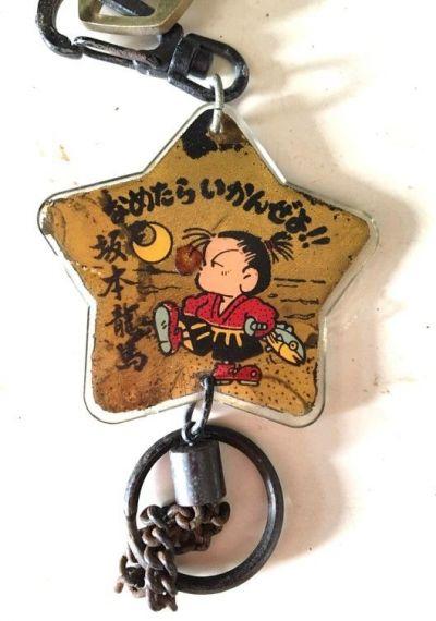 民宿のフロントで見つかった「なめたらいかんぜよ!!」と書かれた坂本龍馬モチーフのキーホルダー。上には客室の鍵がついている。