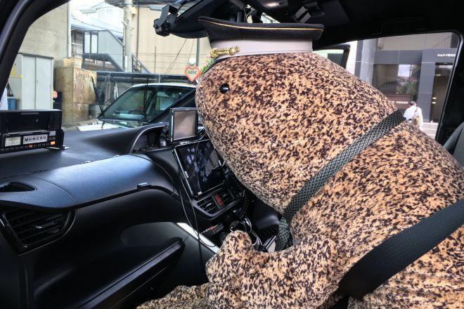 助手席にオオサンショウウオのぬいぐるみを乗せたタクシー