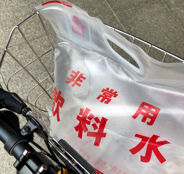 札幌市水道局でもらった6リットルの非常用飲料水。自転車のかごは重みに揺れた=2018年9月6日、札幌市
