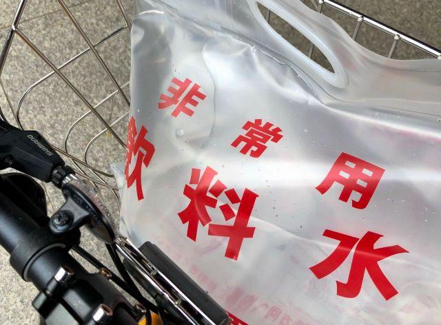 札幌市水道局でもらった6リットルの非常用飲料水。自転車のかごは重みに揺れた=2018年9月6日、札幌市、天野彩撮影