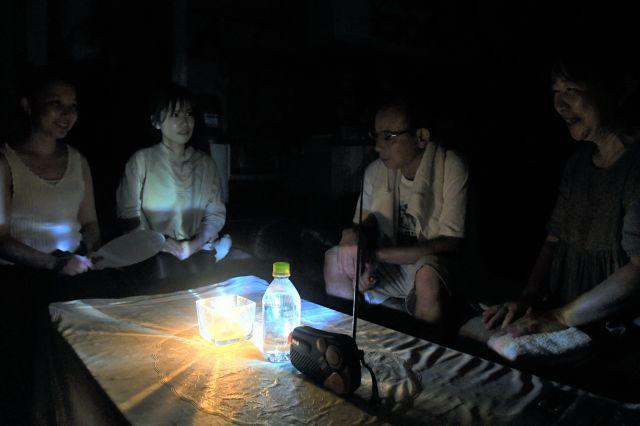 停電が続く中で、ろうそくをともして、ラジオを流しながら会話する家族=2019年9月10日午後8時42分、千葉県君津市、小木雄太撮影