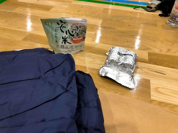 避難所で配られた食料と寝袋。水は配布していなかった=札幌市中央区の公立小学校の体育館