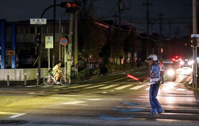 停電が続く中、手信号で交通整理する警察官=2019年9月10日午後6時30分、千葉市緑区、川村直子撮影