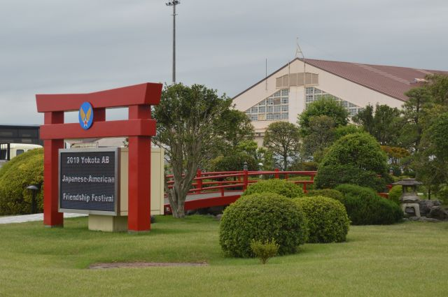 米軍横田基地の滑走路の脇にある鳥居の形をした電光掲示板と、日本庭園風の一角。奥は格納庫