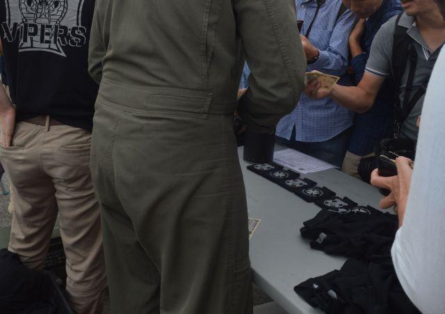 米海兵隊の攻撃ヘリAH1Zの展示の前でグッズを買い求める男性らに応じる兵士ら