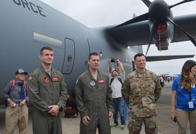 米空軍の輸送機C130Jの前で報道陣の取材に応じるネイサン・ヘデン少佐(中央)ら、横田基地友好祭実行委員会のメンバー3人