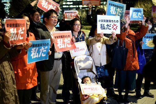 国会議事堂前での抗議行動で「保育園落ちたの私だ」と書かれた紙を持つ人たち。男児の上には「落とされたのオレだ!」の文字も