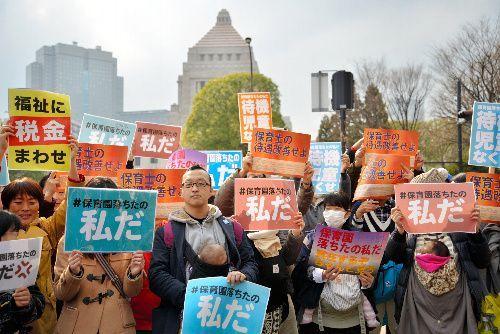 「保育園落ちたの私だ」などと書かれた紙を掲げて立つ人たち=東京都千代田区の国会議事堂前、後藤遼太撮影