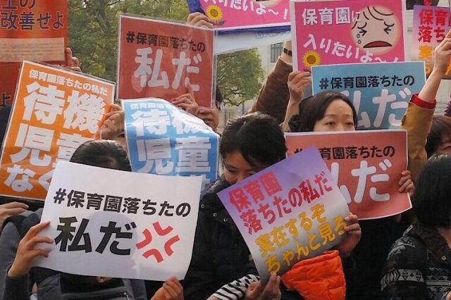 「保育園落ちたの私だ」などの紙を掲げて東京・永田町の国会議事堂前に立つ人たち=2016年3月5日