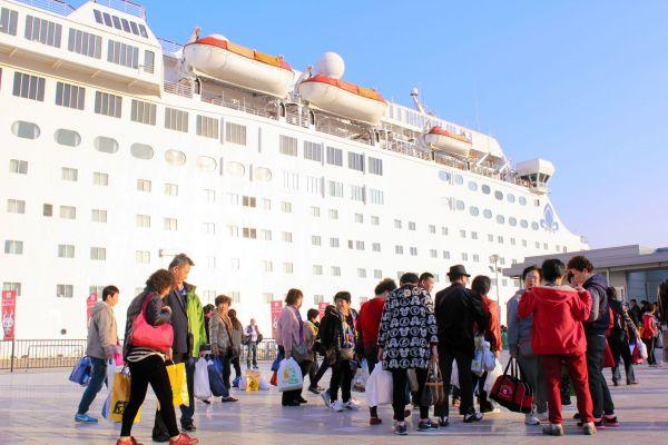 たくさんの土産を抱えて船に戻る中国人観光客=2014年11月20日、別府市の別府国際観光港