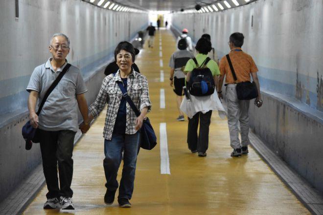 関門トンネルの人道を手をつないで歩く日吉正勝さん(左)と妻の洋子さん=9月25日、関門トンネル、山田菜の花撮影