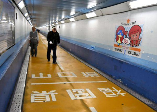 関門トンネル人道の県境には、開通60年を記念して、赤いちゃんちゃんこを着たフグと関門ダコのイラストもお目見えした