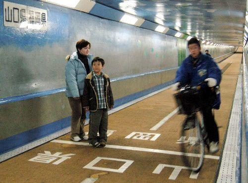 人道トンネルの県境に立つ親子ら=関門トンネル人道で