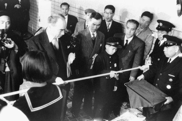 関門国道トンネルが開通し、人道の渡り初めをした山口県下関市と現在の北九州市門司区の子どもたちが中央部でテープカットを行った=1958年3月9日