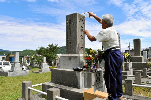 ヒグマが駆除され、お墓参りをする男性。「お参りに来られてよかった」と墓石に水をかける=札幌市南区の藤野墓地