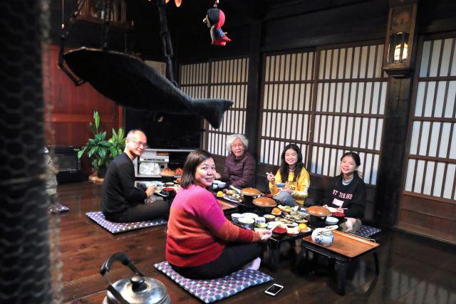 合掌造りの民宿で夕食をとる、シンガポールから訪れた家族連れ=2018年12月、岐阜県白川村、吉本美奈子撮影