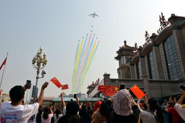 カラフルな煙を出しながら飛ぶ航空機=北京、2019年10月1日