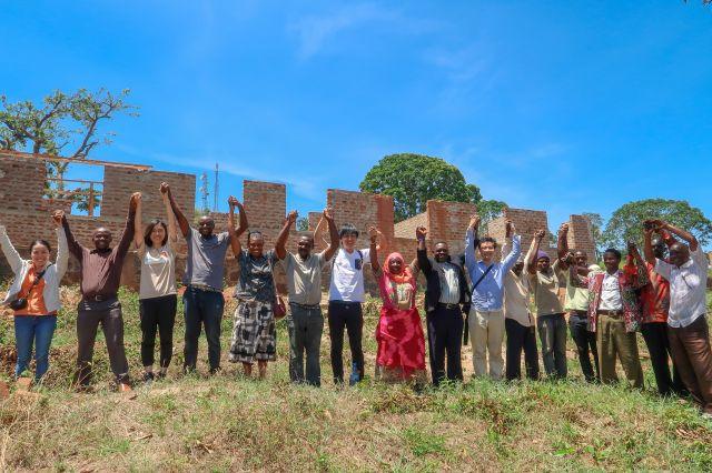 病院建設予定地で手をつなぎ合うあおぞらのスタッフと、タンザニアの人たち=あおぞら提供