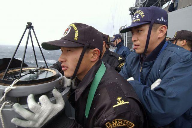 15年前に筆者が同乗した練習艦「かしま」での海自幹部候補生らの訓練。羅針盤を見つつ「蛇行運動」に取り組む=2004年2月、日本海