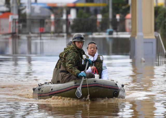 台風19号のため長野市で浸水があった地区から男性をボートで救出する陸上自衛官=10月14日