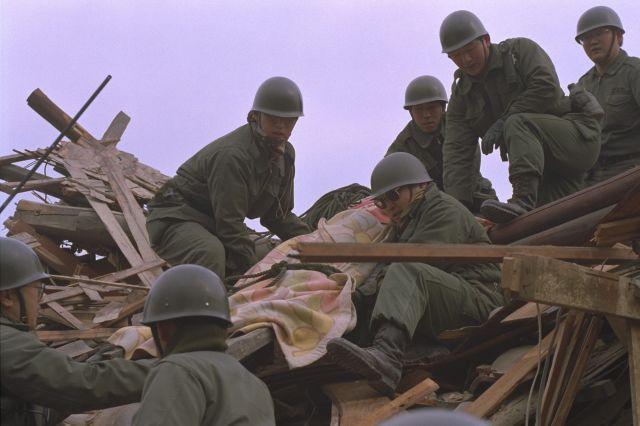 阪神大震災で倒壊した住宅から遺体を運び出す陸上自衛官ら=1995年1月18日、兵庫県西宮市