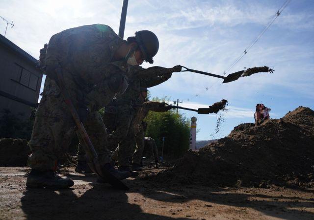 台風19号災害で道路に流れ込んだ土砂を除去する陸上自衛官ら=10月17日午前、宮城県丸森町