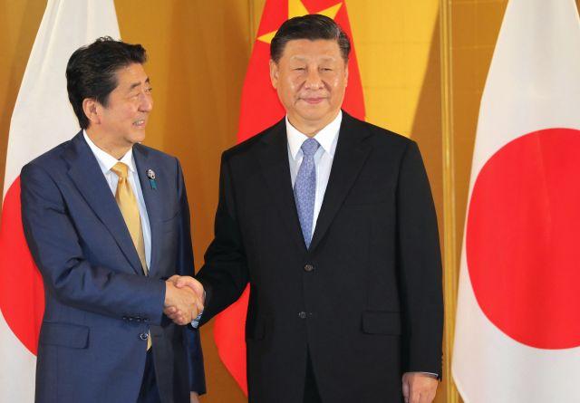 中国の習近平国家主席(右)と握手する安倍晋三首相=2019年6月27日午後7時34分、大阪市北区、代表撮影