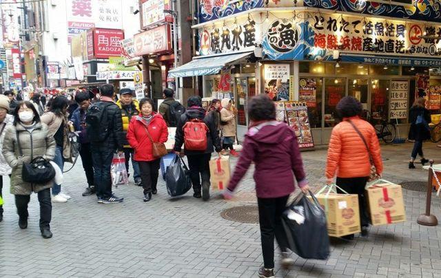両手に家電製品を持ち、大阪・ミナミを観光する中国人たち。炊飯器は「爆買い」の象徴だった=2017年1月、大阪市中央区