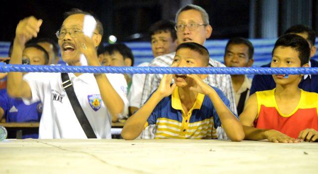 ムエタイの試合中、リングサイドでは家族やジムの関係者らが戦う少年ボクサーに声をかける=2019年10月、バンコク・バンパコン