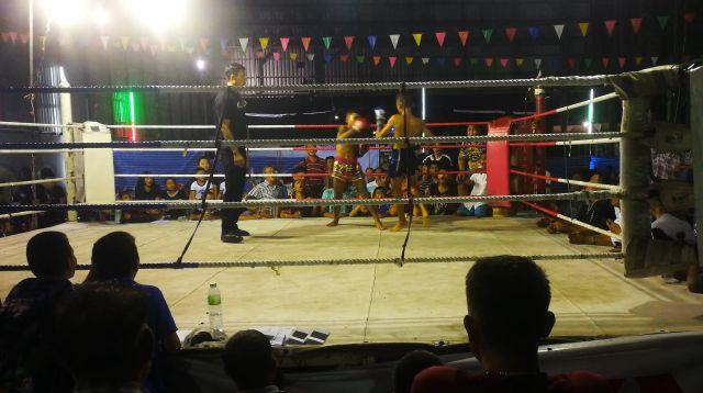 多くの観客に取り囲まれたリングで試合をする少年たち=2019年10月、バンコク・バンパコン