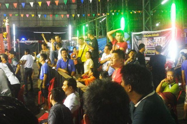 リングサイドで、観客たちは声を上げる。左手奥の男性のように合図をして、賭けに参加しているという=2019年10月、バンコク・バンパコン