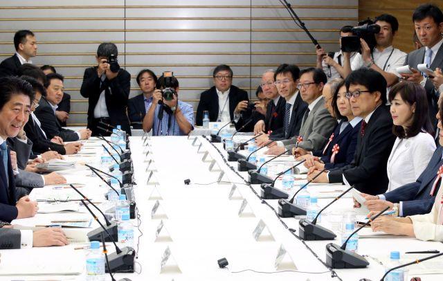 1億総活躍国民会議であいさつする安倍晋三首相(左)。菊池桃子氏(右)と新原浩朗氏(中央奥カメラマンの右)も同席していた=飯塚晋一撮影