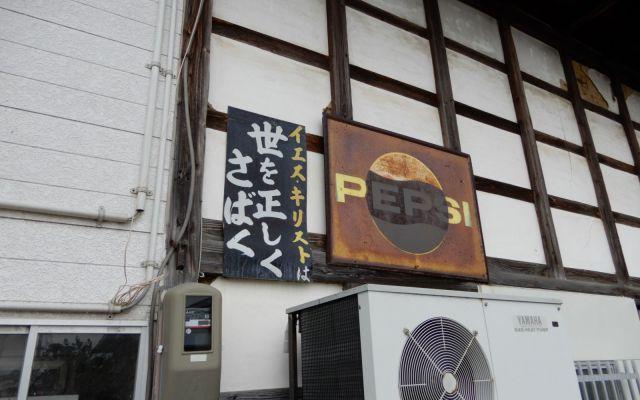 商店の壁に貼られた、古びたキリスト看板。オーナーが不在だったため貼り替えは断念した