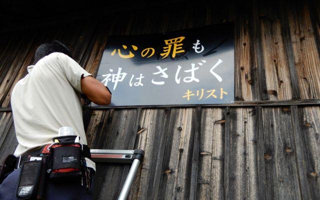 長はしごに乗って看板を貼る。手慣れた作業ぶりは、まるで本物の外装工事業者