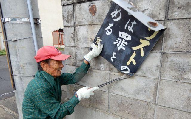古い看板をバールで剥がす田中さん。伝道キャリアが長いだけに、作業はお手のもの