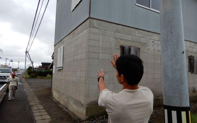 絶好の設置ポイントを見つけた朝岡さん。家主との交渉前に、貼る位置と大きさ、文言をイメージする