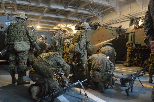 離島奪回訓練で水陸両用車(奥)に乗り込む前に準備する陸自水陸機動団の隊員ら=11月14日午前、太平洋上の海自輸送艦「くにさき」艦内