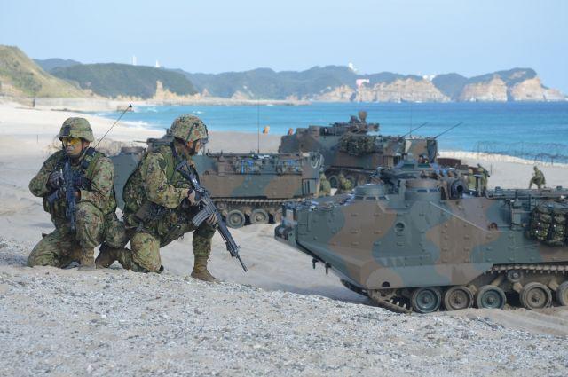 離島奪回訓練で砂浜に陸自の水陸両用車で上陸し、展開して銃を構える隊員ら=11月14日午後、鹿児島県・種子島の前之浜