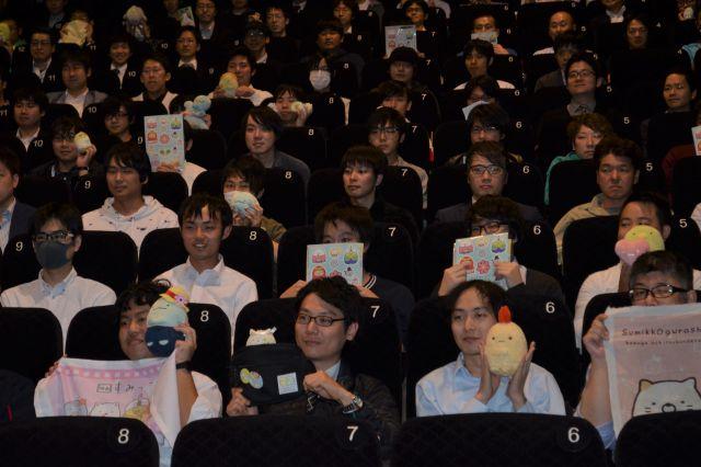 写真撮影で笑顔を浮かべる観客ら