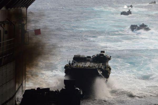 黒煙を上げ、荒れる海へ次々と発進する陸自の水陸両用車=11月14日午前、太平洋上の海自輸送艦「くにさき」艦内
