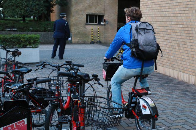 朝日新聞東京本社前のポートで自転車を借りる男性。=11月21日、瀬戸口翼撮影