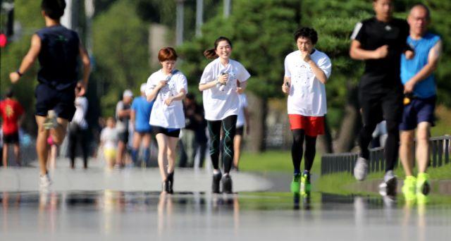 暑さで「逃げ水」が浮かぶ中、皇居外苑の二重橋前を走る人たち=2019年8月9日、東京都千代田区、長島一浩撮影