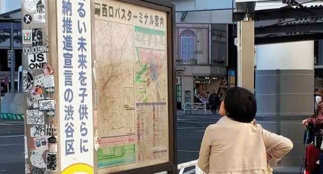 西口のモヤイ像前のバス乗り場の地図を見つめる高重記者