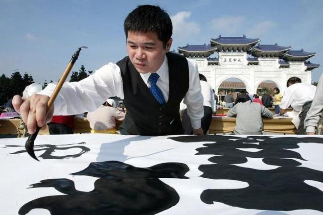 巨大な布の上で揮毫する中国の書道家=2013年8月30日、瀋陽、遼寧省=ロイター