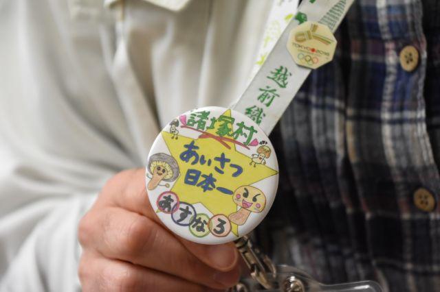 村の小中学生が考案した「あいさつ日本一」のバッジ。村教委の職員らが身につけている=2019年11月