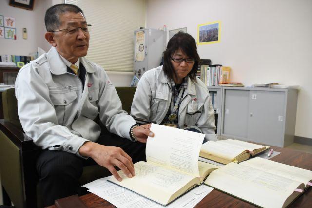 村の成人式の歴史を説明する甲斐誠教育長(左)と、成人式担当職員の伊藤聖子さん=2019年11月