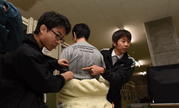 石棒クラブのTシャツで制作過程を説明する三好清超さん(右)